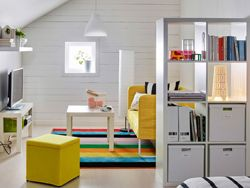 A teenage room with a white shelving unit used as a room divider