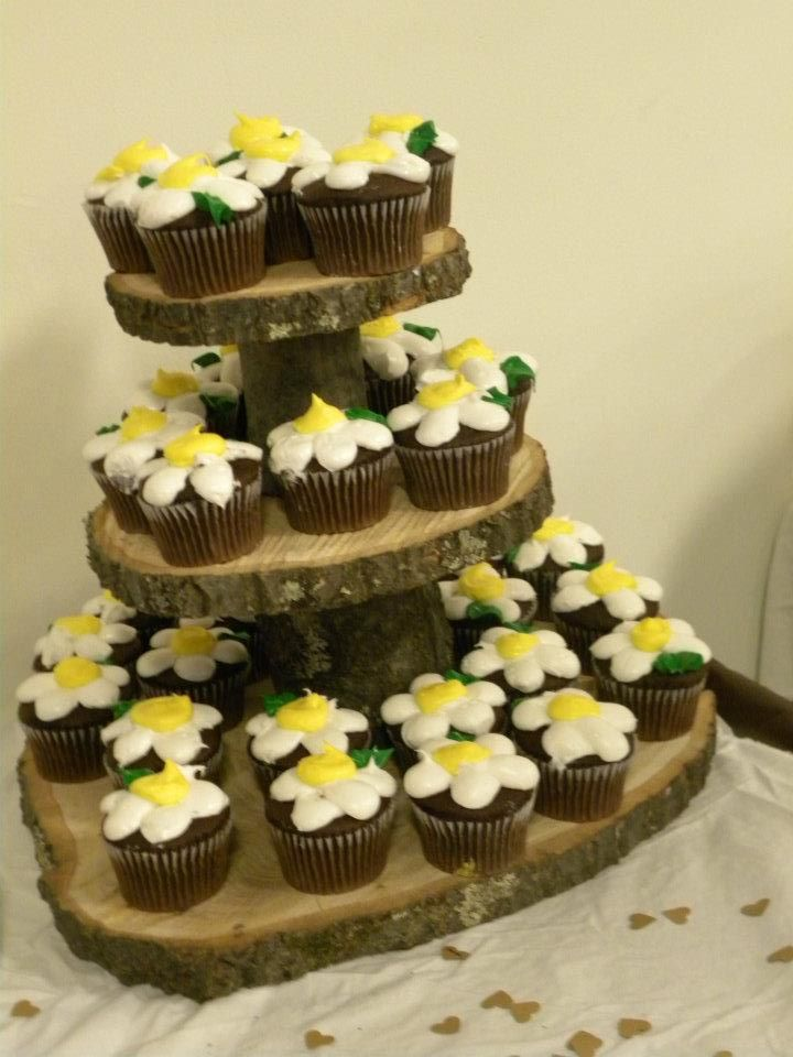 second log/wood cupcake stand with chocolate cupcakes topped with ...