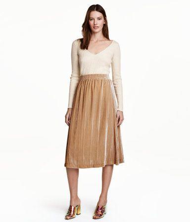Beige. Een knielange, uitlopende rok van zacht fluweel met elastiek in de taille. Gevoerd.