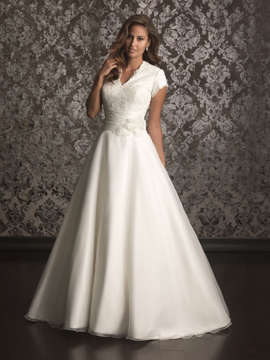 Still in love with this one. A romantic A-line gown featuring lace and organza. The fitted bodice has a flattering v-shaped neckline and covered back in lace while the waist is defined by a ruched band and flowers. See store for sizing and availability.