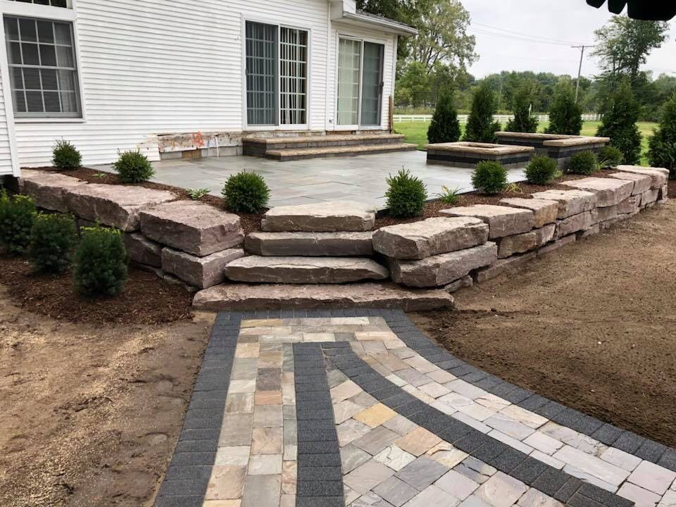 Outcropping Stone Retaining Wall Landscaped With Boxwoods Banas Stone Natural Pavers Landscaping Retaining Walls Landscape Design Services Raised Patio