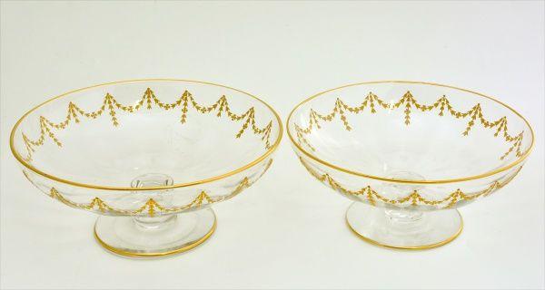 BACCARAT - Par de fruteiras em cristal soprado, ornamentadas com arabescos em ouro. França. Século XIX. 09 x 23 cm e 10 x 25 cm.