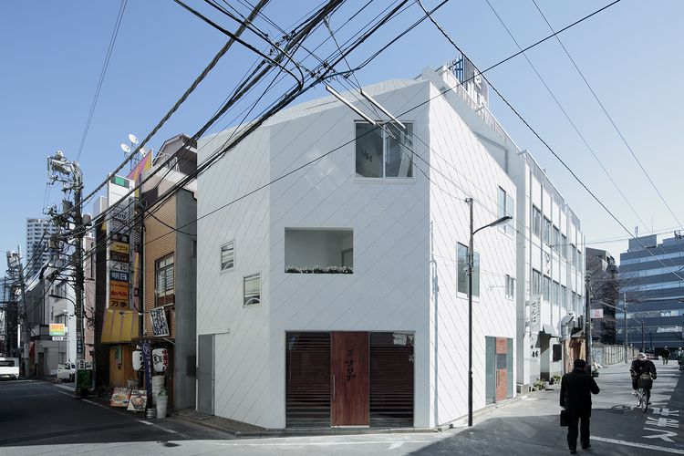 """The buildings stands on a corner used as a resting point during the annual festival, and the clients wanted to create a dramatic background for the colorful floats. The white """"stealth"""" shape, looking almost like folded origami, is clad in trapezoidal shingles of painted metal and stands out against the dingy browns and grays typical of Tokyo neighborhoods…"""