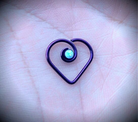 This beautifully designed 18g Niobium Heart with Opal is a luminous ring with a decorative synthetic opal that will look stunning in your piercing. The Niobium Heart with Opal is handmade and hand polished by our on-staff jeweler for a unique style with a