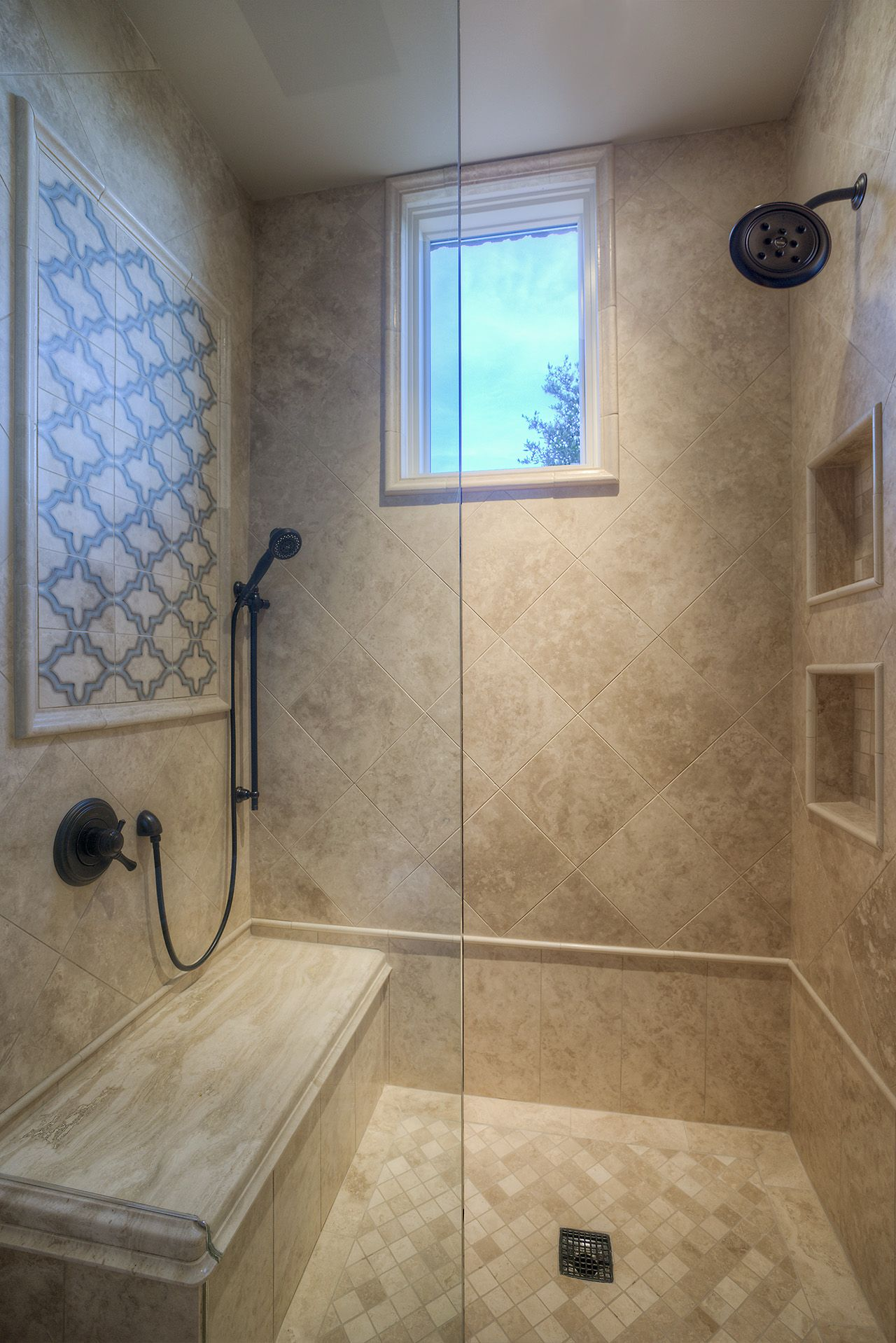 custom luxury walk in shower with two shower heads and accent tile work