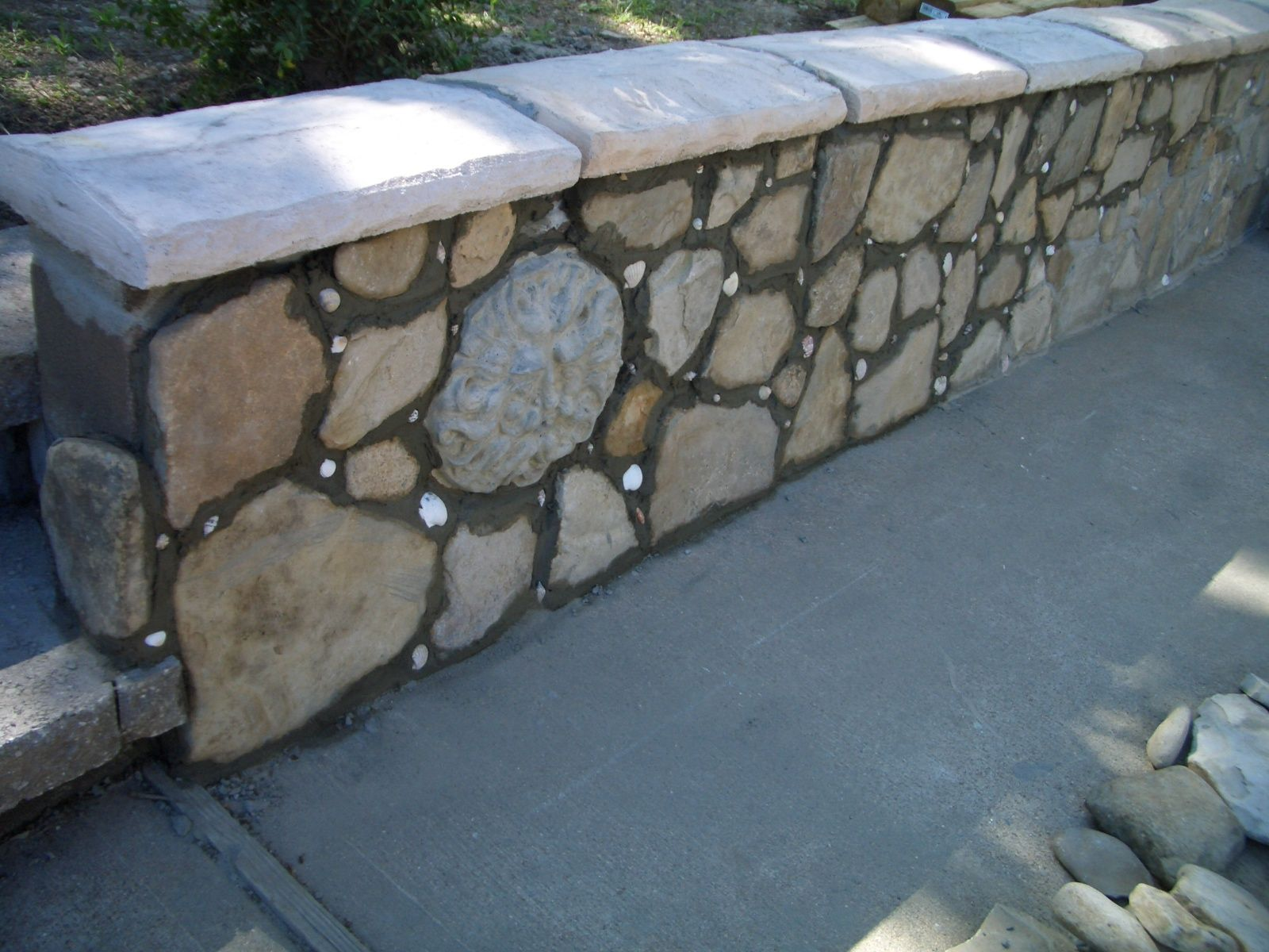 Another View Of The Retaining Wall Along The Driveway Faced W River Rock Seashells And Cement Faces And Stone Retaining Wall Curb Appeal Garden Farm Gardens