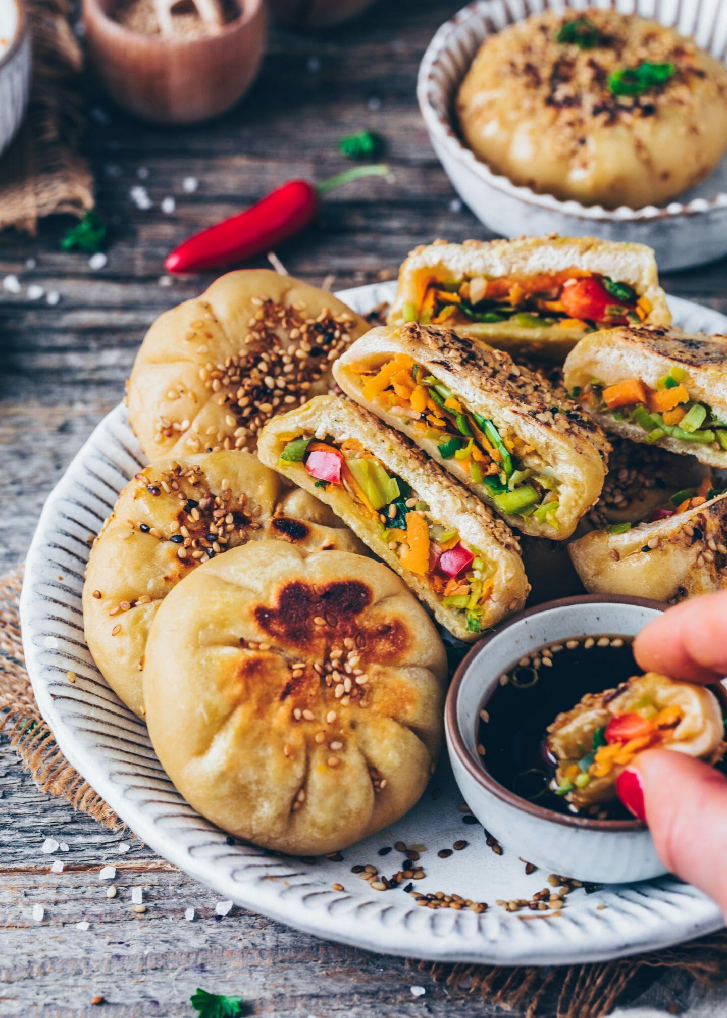 """Wenn du vegane Teigtaschen wie Chinesische Dumplings (Gyoza), Ravioli oder Baozi liebst, wirst du auch dieses Rezept für knusprig gebratene, gedämpfte Gemüse-Brötchen lieben! Diese Baozi Buns werden auch """"Sheng Jian Bao"""" genannt und sind gesund gefüllt mit viel Gemüse statt Fleisch. Dieses Rezept enthält auch eine Schritt-für-Schritt Anleitung, wie du Hefeteig ohne viel Aufwand herstellen kannst!"""