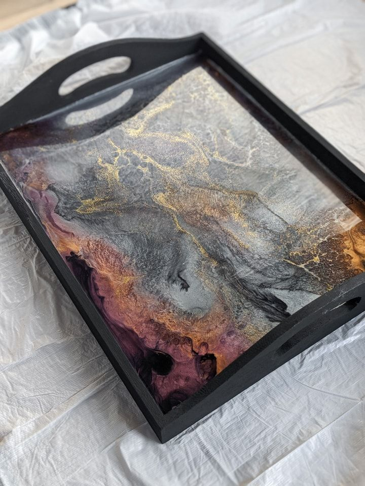Learn how to make a beautiful DIY resin and wood serving tray. Embellishing a wooden tray with marbled resin is easy and has a beautiful effect. #resin