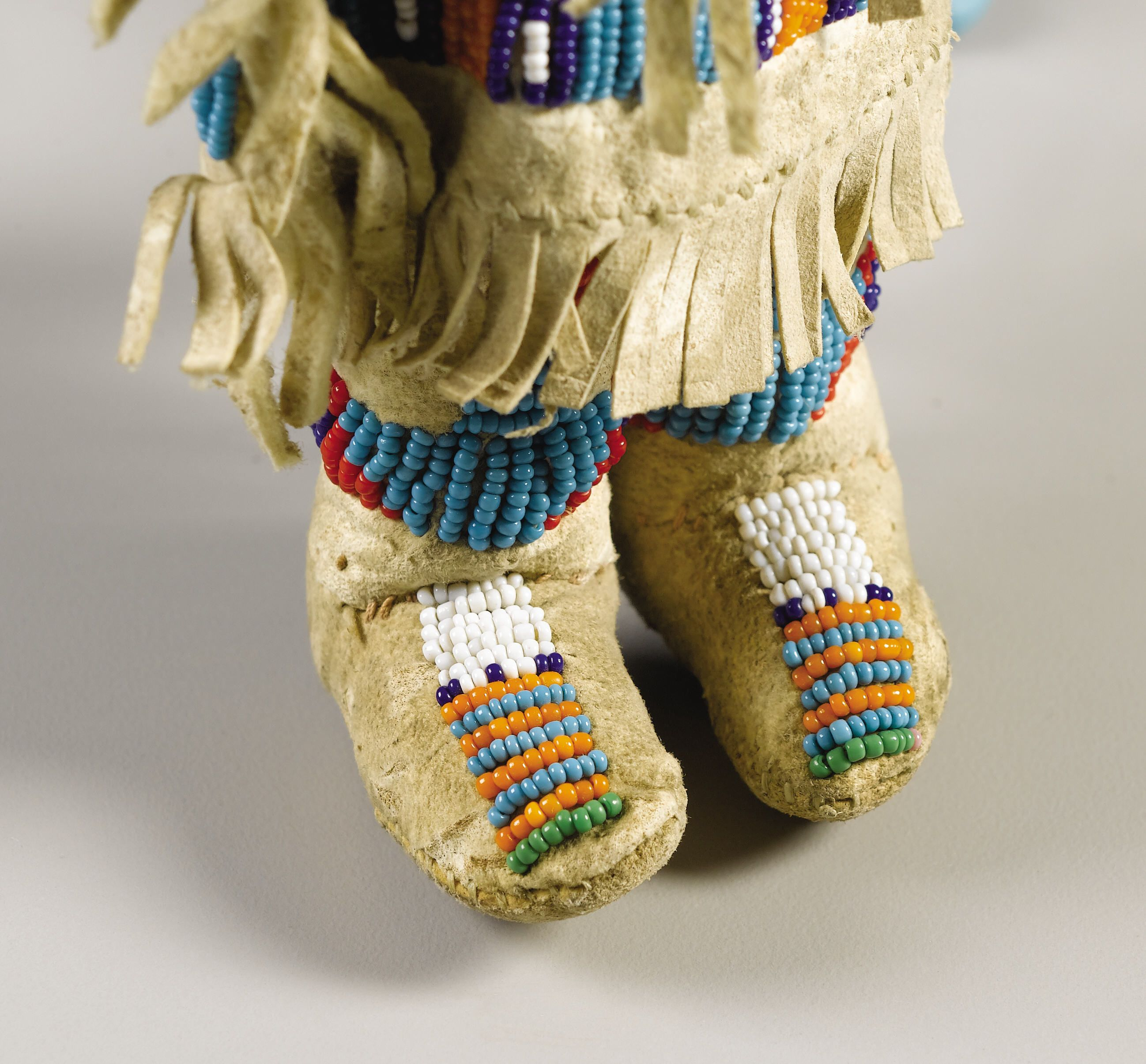 A SIOUX BEADED HIDE FEMALE DOLL. . c. 1900. American