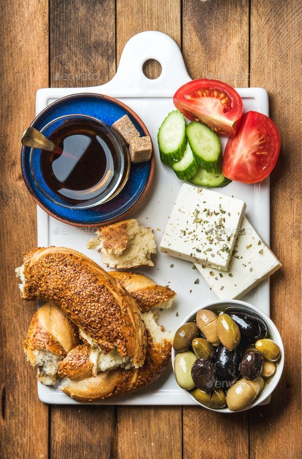Turkish traditional breakfast with feta cheese, vegetables, olives, simit bagel and tea by sonyakam