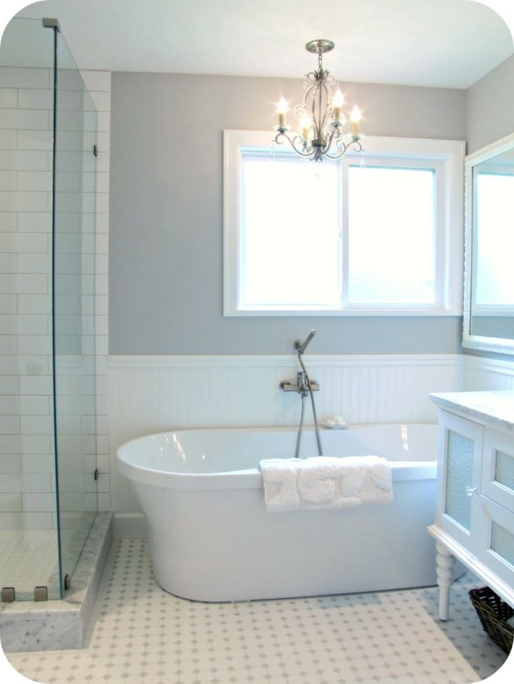 Bathroom. oval white bath up with shower on the white floor beside ...