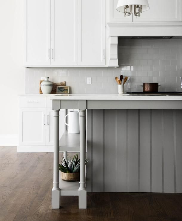 A Gray Shiplap Kitchen Island Accented With Turned Legs And Under Counter Shelving Is Topped White Quartz Countertops Illuminated By Nickel Shaded