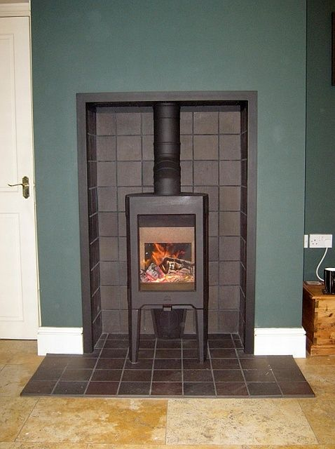 This fireplace has already been altered and tiled with black quarry tiles  and is crying out for a tall contemporary stove with three sided glass. - Woodburner Inset And Hearth Tiled With Handmade Terracotta Tiles