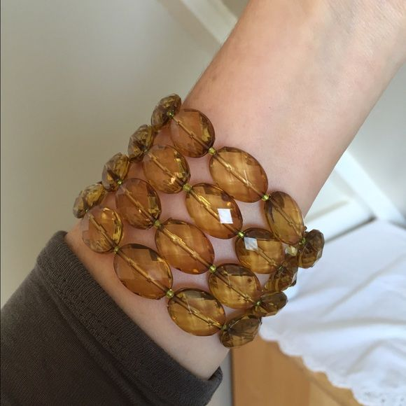Anthro Amber-colored statement bracelet Four strands of faceted Amber-colored heavy, quality plastic beads with an antiqued-brass-colored magnetic closure. EUC. (Anthro necklace, UO wrap, and dress pictured here are also for sale in my closet ) Anthropologie Jewelry Bracelets