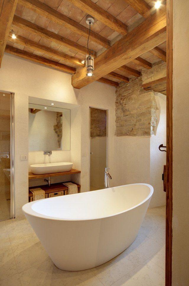 une baignoire îlot blanche et un plafond en bois dans la