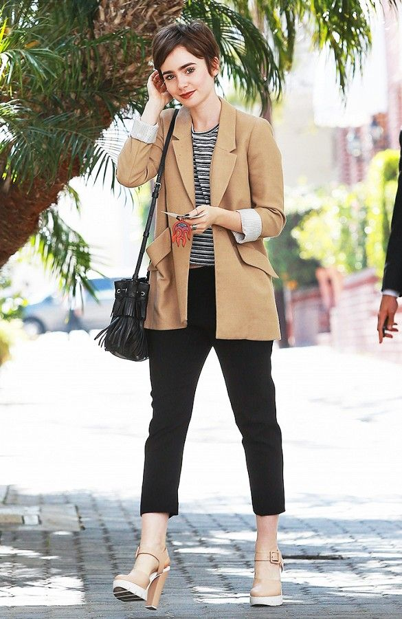 5032a3214ba9 Lily Collins wears a striped top, camel blazer, sleek black cropped  trousers, nude and white heels, and a black tassel bucket bag