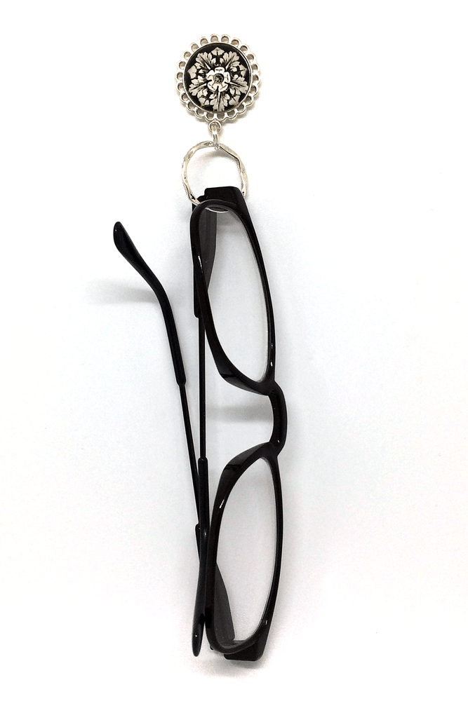 20a3364abafa Classic black and white design is festive on this magnetic eyeglass holder.  A lovely white