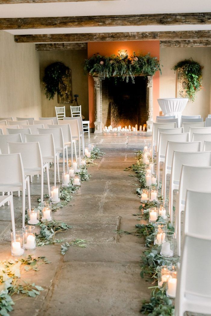 Scattered eucalyptus and candles in vases lining the outside ends of each row