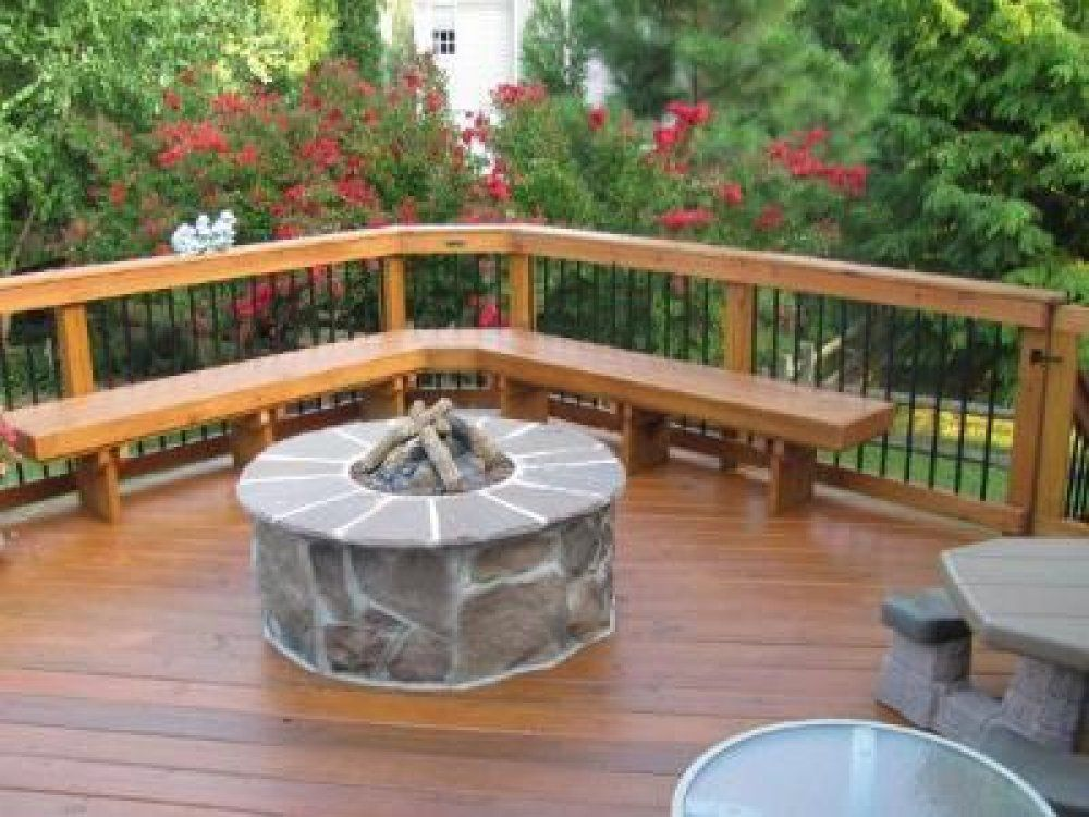 Hereu0027s A Wooden Deck With A Stone Fire Pit In The Middle.