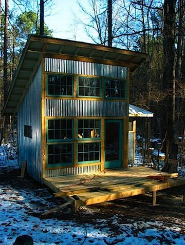 Two Story Tiny House With Corrugated Galvanized Siding And Green Painted  Windows.