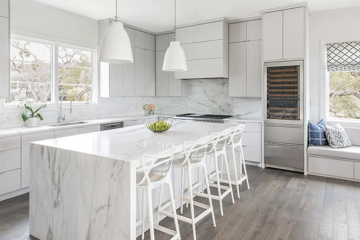 White dome lights hang over a white quartz waterfall countertop accenting a light gray island seating four DWR Master Barstools facing a stainless steel sink with a polished nickel gooseneck faucet mounted beneath a window. #waterfallcountertop