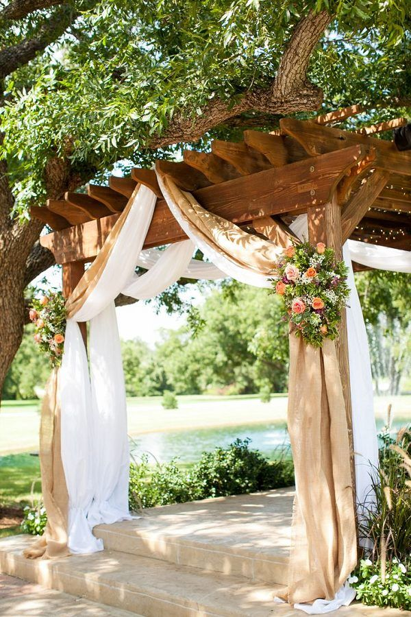 burlap draping with country pink and green flowers over a wooden pergola http