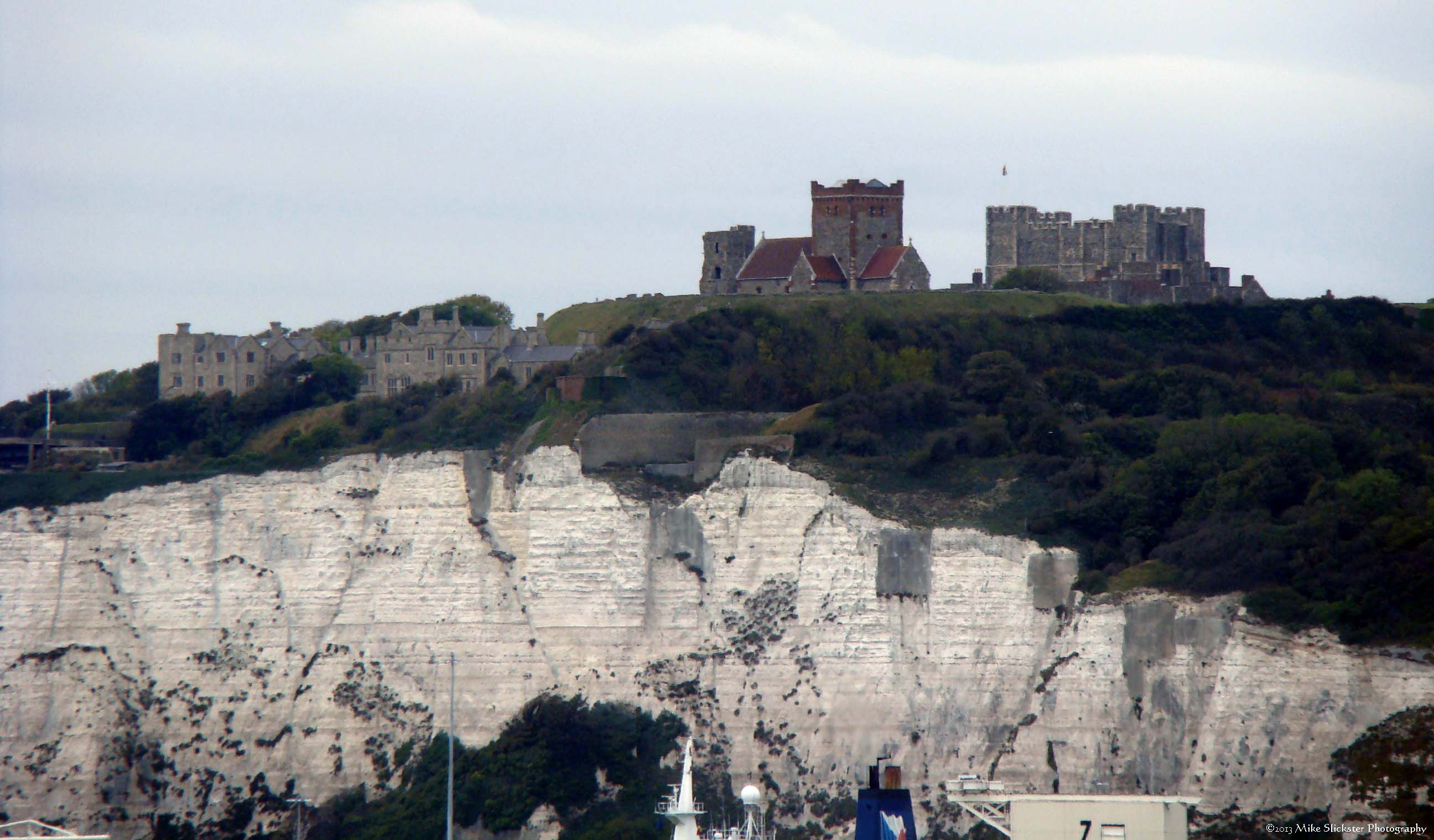 Castle and white cliffs below it, as seen from the ferryboat at the departure across the English Channel to France.