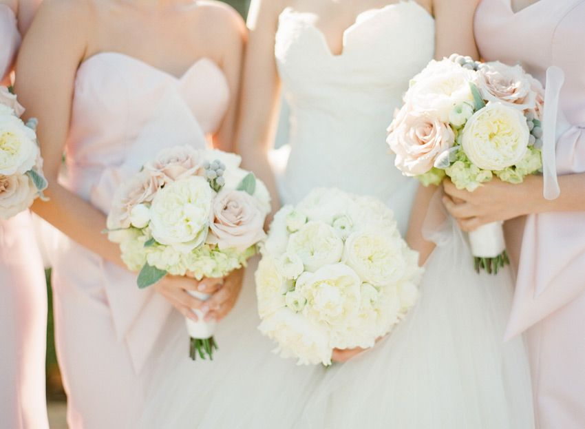 a white bouquet for the bride and mixed pastel bouquets for the bridesmaids flowers