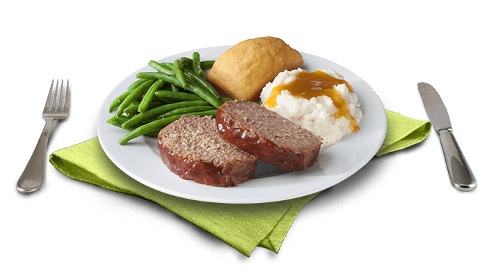 Two slices of meatloaf on plate with two sides and