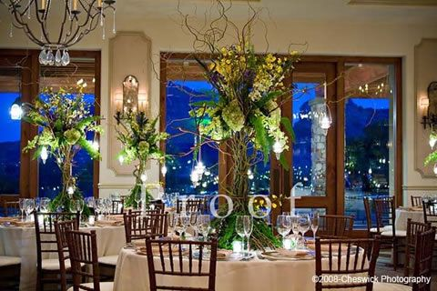 Tall centerpiece with brown willow sticks, leaves, green and white floral