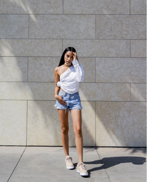 7 fashionable outfit ideas to try before summer ends, from the best dressed bloggers on Instagram: Aleali May in denim cutoffs, sneakers and a white one-shouldered button down shirt