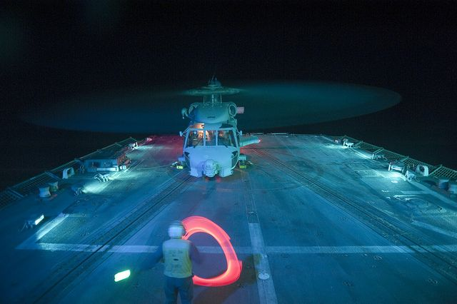 A Sailor directs an SH-60B Sea Hawk helicopter. by Official U.S. Navy Imagery