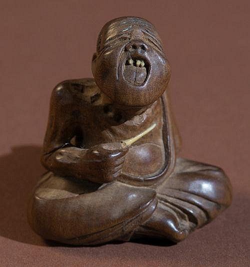 Netsuke, wood and horn. Japan, 1st half of 19th cent. The professional sneezer who sits on the street tickling himself and then nearly explodes to amuse the bystanders. This motif is quite common, the facial expression on this figure is particularly well-made, realistic and grotesque! Very vivid anatomical details, the small rod and some of the upper teeth are made of horn. Unusually large himotoshi, the signature MI-WA with the typical seal. Very good condition. HEIGHT 3,85 CM
