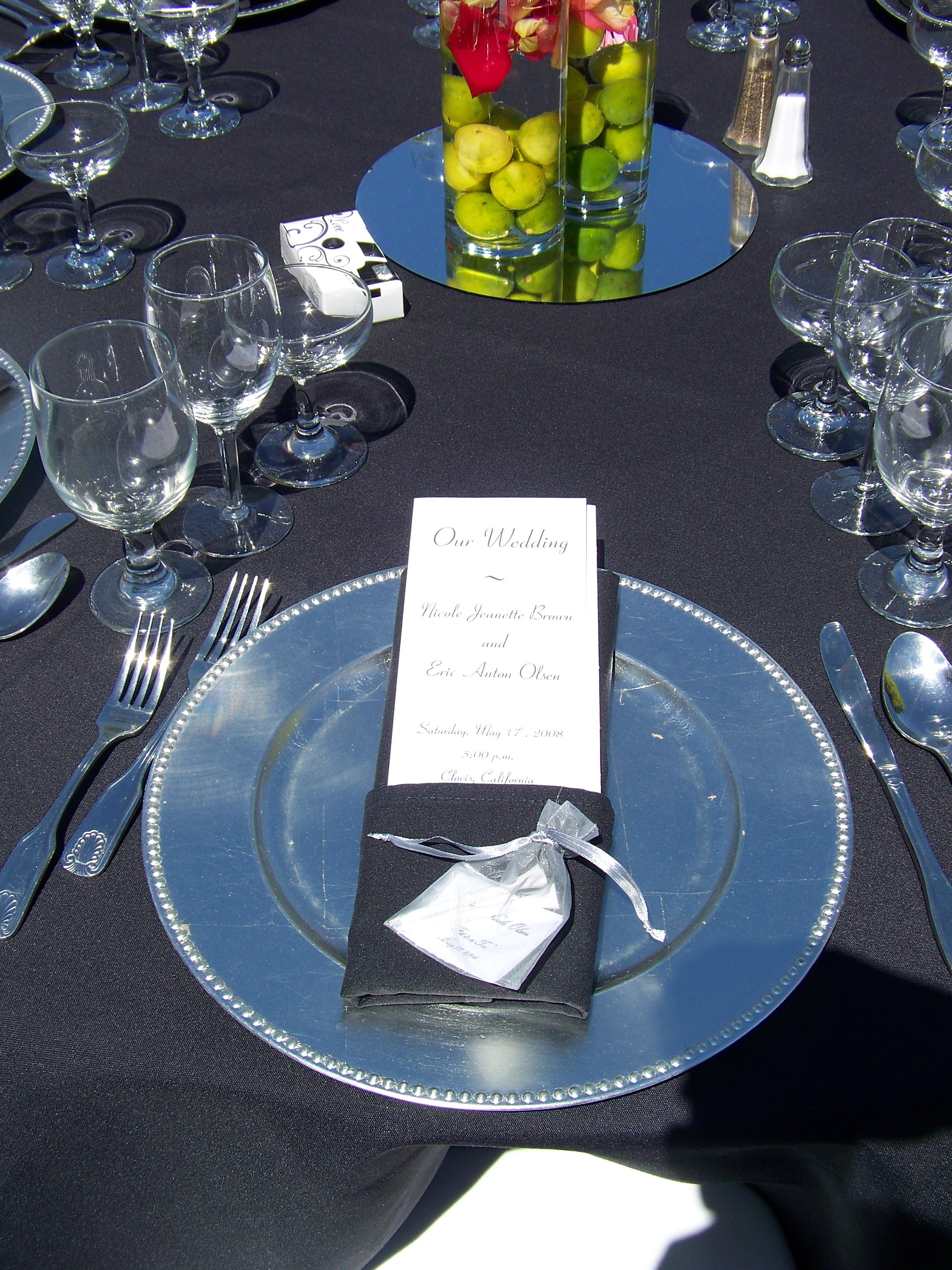 """Placesetting / Satin 120"""" Linens in Black / Crystal Stemware / Silver Chargers / Menu Cards tucked into Custom Folded Black Napkins / Wedding Favor on Menu Card / Fruit Filled Centerpieces w/ Floral on top of a Circle Mirror"""