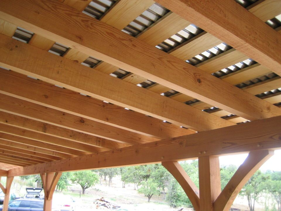 Ceiling Of The Timber Porch Constructed Of Pine Skip Sheathing Over 3 X 8  D. Galvanized Corrugated Metal Roofing Is Visible