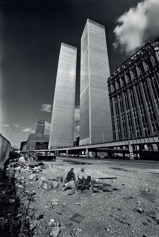 Two homeless men squat in the shadow of the then-recently completed World Trade Center towers circa 1972.