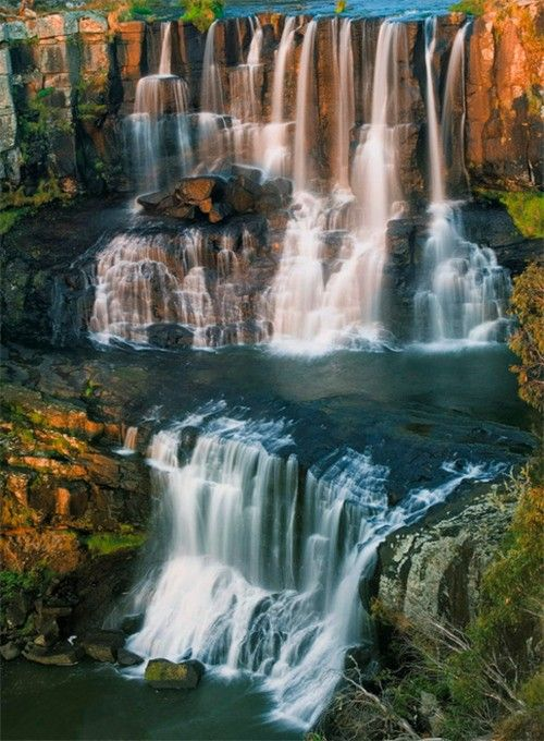 Ebor Falls in New South Wales, Australia. Made up of an upper (shown) and lower falls, the upper is a 115m high double waterfall over basalt columns. Nearest town is Ebor.