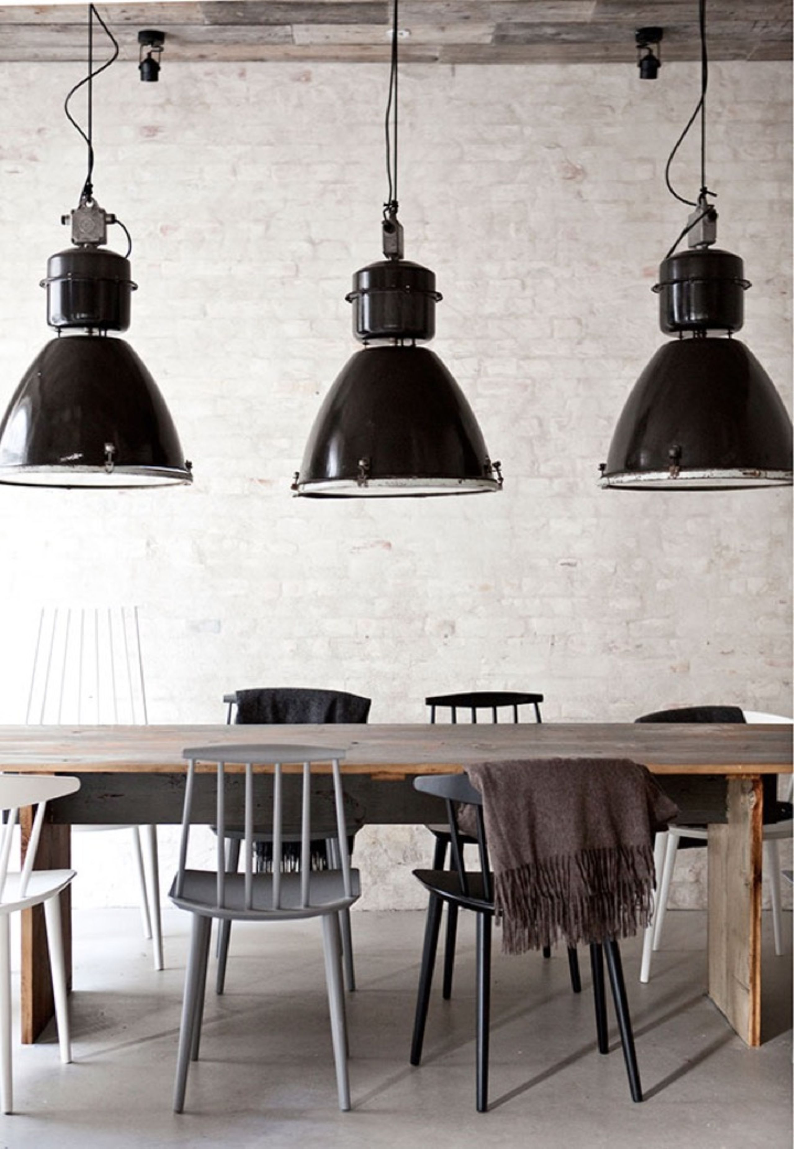 Minimal interior design idea with huge pendant lights, wood table and different style chairs