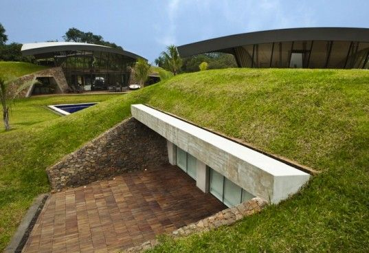 Two Homes Tucked In The Ground Are Topped With Sweeping Arched Roofs In Paraguay Container House Design Earth Sheltered Homes Underground Homes