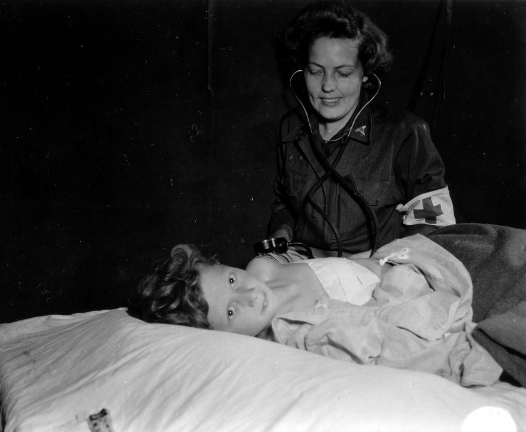 A nurse from the ANC (ARMY NURSE CORPS. Corps military nurses) at the bedside of a little girl, with a stethoscope.