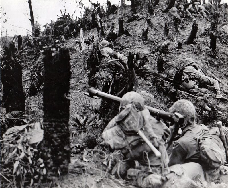 Two Marines armed with a Bazooka inch their way up a hill 2 miles north of Naha during the Battle of Okinawa. (National Archives