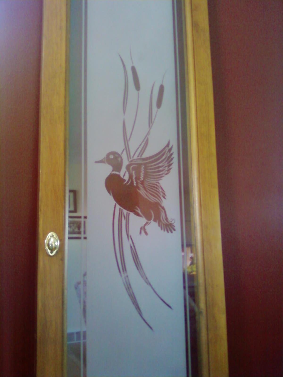Cabinet door with etched scene of duck in flight onto ...