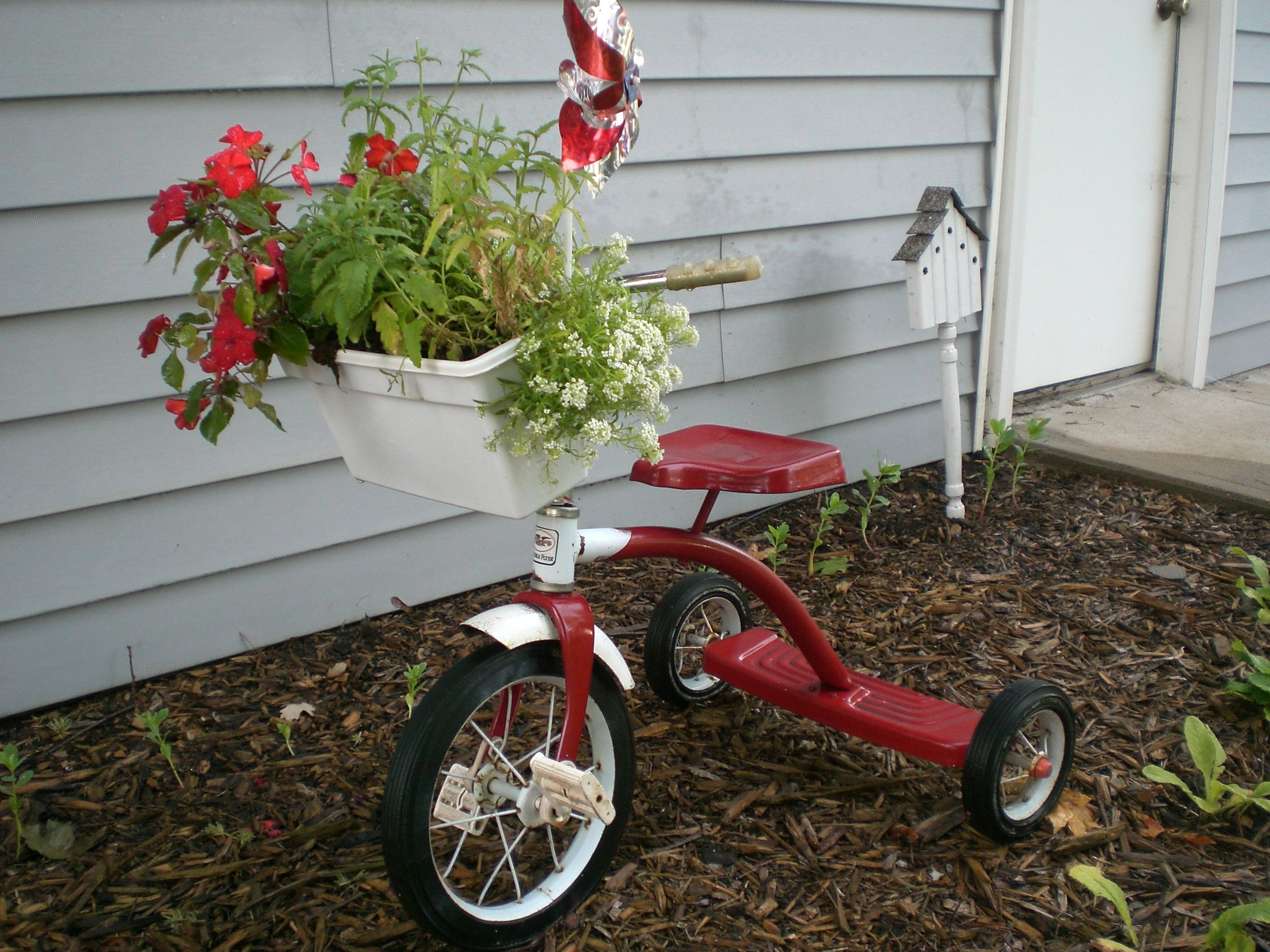 Garage sale trike with planter made out of a freezer container for ice cubes.