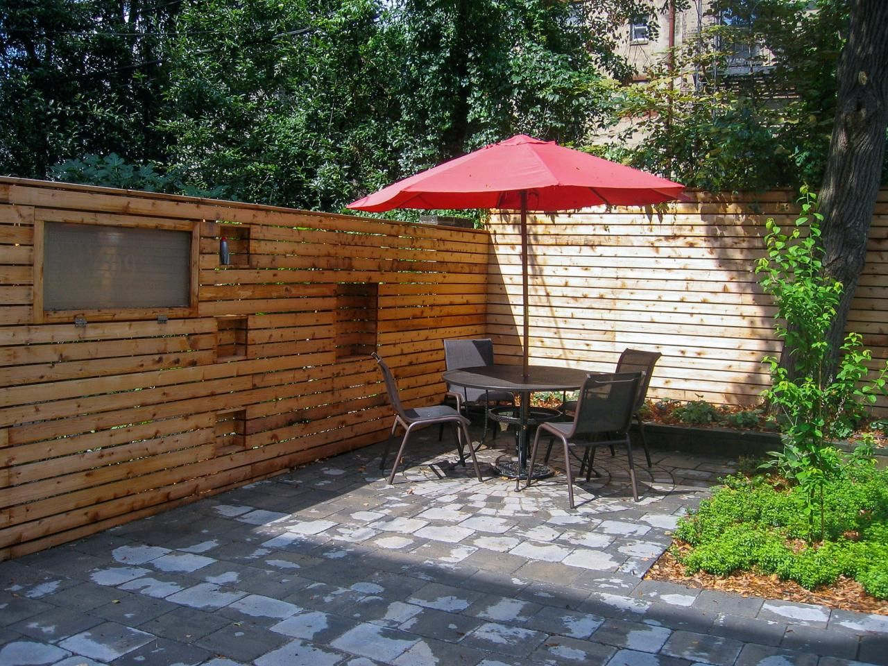 a custom built wood plank wall encloses the stone patio of this