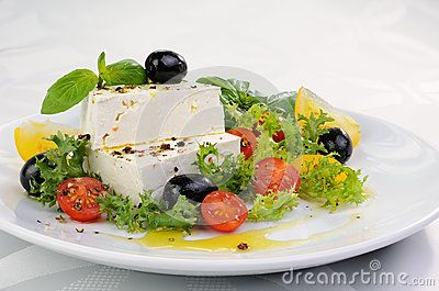 Cubes of feta cheese in oil with spices, cherry tomatoes and olives