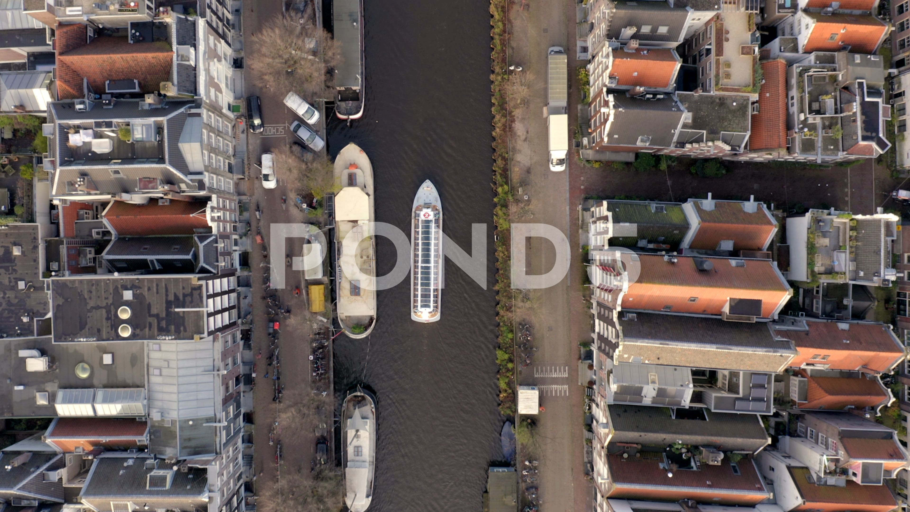 Canal Boat Tour in Amsterdam Amongst Riverside Houses Birds Eye View Stock Footage AmsterdamRiversideTourCanal