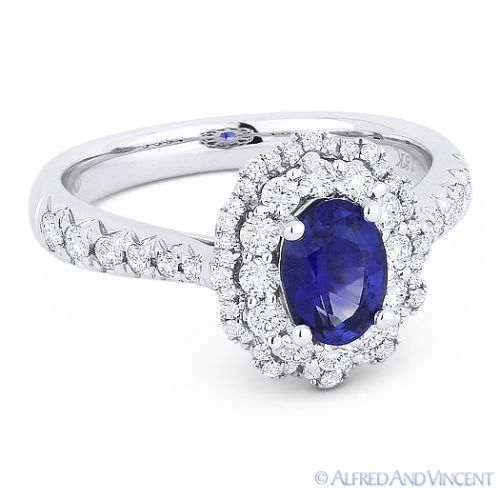The featured ring is cast in 18k white gold and showcases an oval blue sapphire center gem accentuated by round cut diamonds all the way around the double-halo design and halfway along the ring's shoulders.