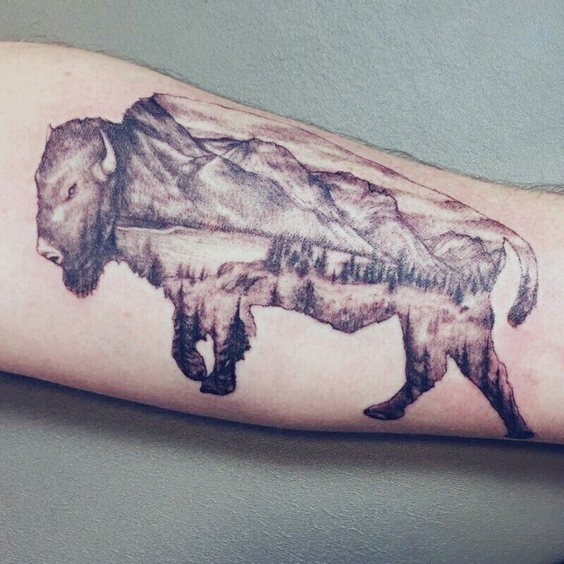 Double exposure bison tattoo with landscape image of St Mary Lake in Glacier Park.