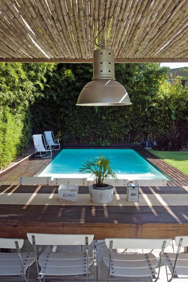 En el jard n la pileta rodeada de un deck de madera y for Choza de jardin de madera techo plano