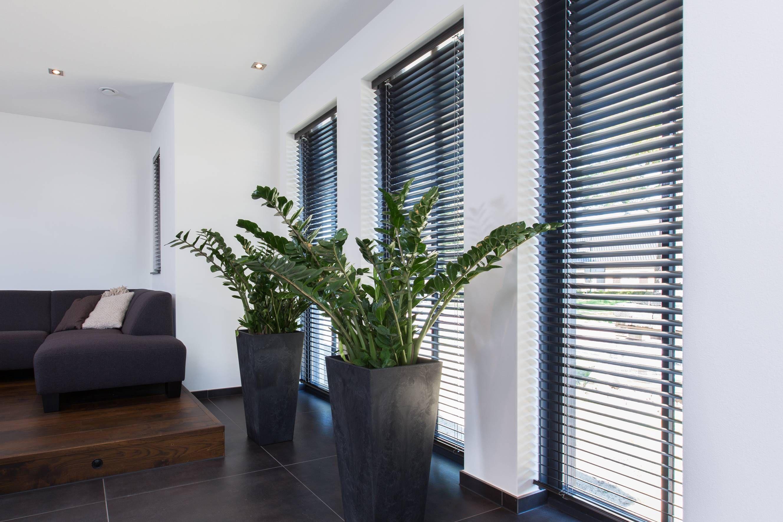 In deze moderne woonkamer zijn zwarte jaloezieën van aluminium